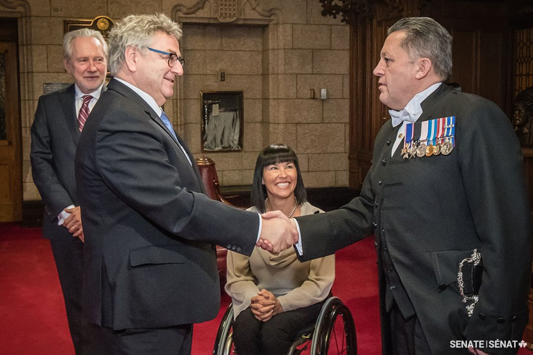Senator Éric Forest, pictured being greeted by the Usher of the Black Rod, Senator Chantal Petitclerc, and Senator Peter Harder.