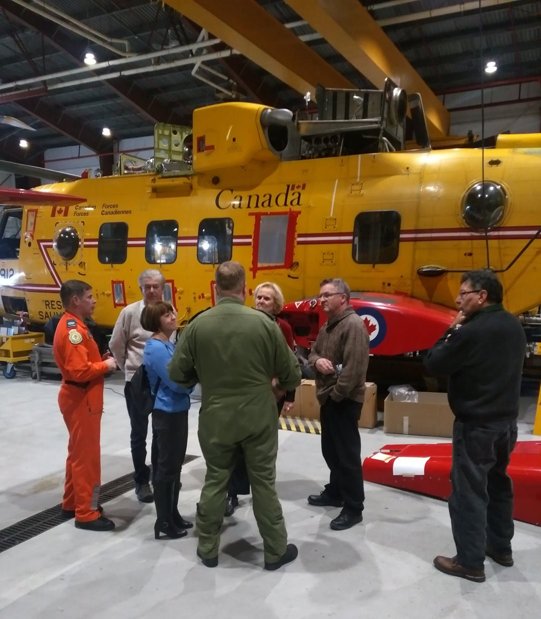 103 Squadron commanding officer Major Jim Pinhorn briefs senators on Cormorant search and rescue helicopters at Canadian Forces Base Gander.