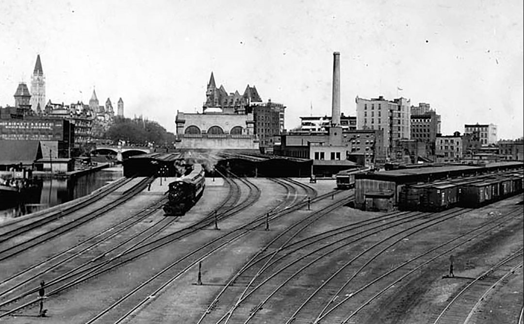 Passenger rail lines used to run into downtown Ottawa along the Rideau Canal. Passengers disembarked at Union Station, now the Government Conference Centre, under the steel-and-glass train sheds in the centre of the photo. An adjacent freight railyard occupied what is now the Rideau Centre shopping mall.