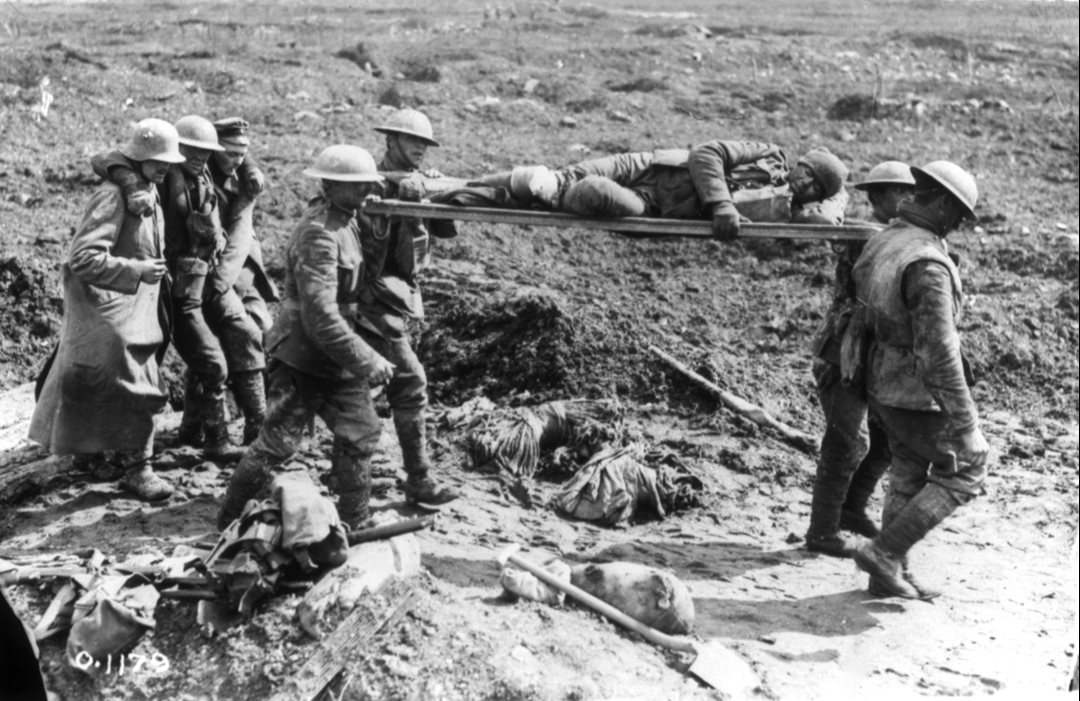 Canadian stretcher bearers and their German captives assist in carrying the wounded off the battlefield. (Library and Archives Canada)