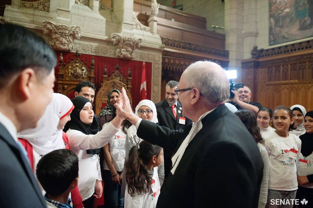 Speaker George J. Furey meets with Syrian refugee children in the Senate Chamber.