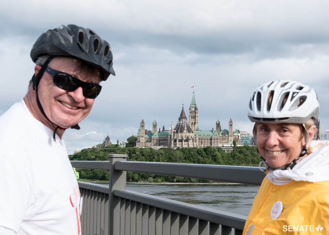 Senators Patterson and Raine share a moment with Parliament in the background.