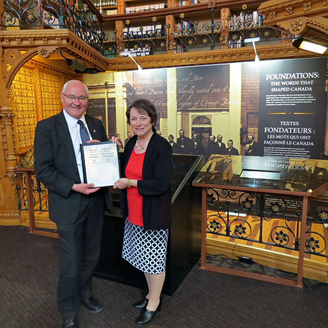 Senator Diane Griffin hands off Bill S-236, the <em>Recognition of Charlottetown as the Birthplace of Confederation Act</em>, to House of Commons sponsor MP Wayne Easter in the Library of Parliament, Ottawa.