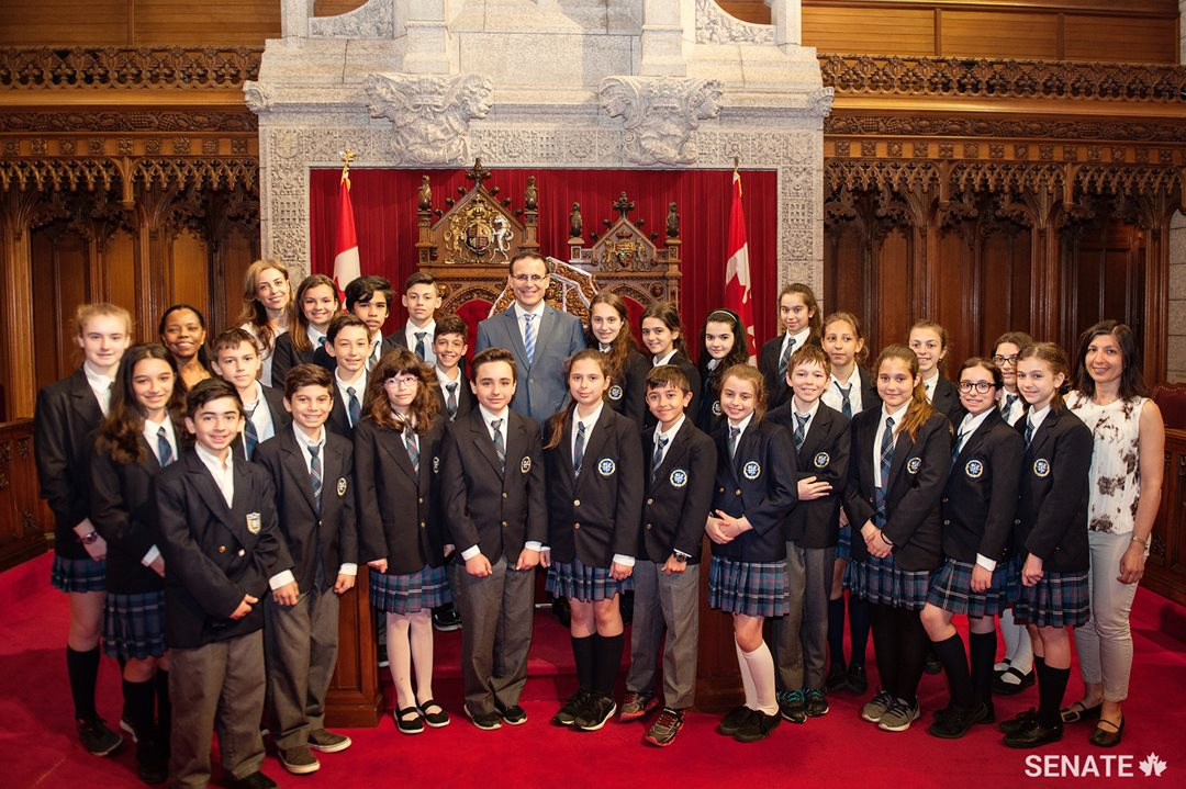 Students from the Socrates-Demosthenes school join Senator Housakos for a group photo in the Red Chamber.