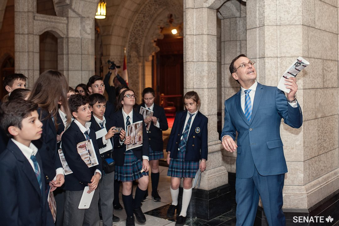 Pointing out the portrait of the King George VI, who overcame a stammer to lead the Commonwealth during the Second World War, Senator Housakos reminds students that they can do anything they put their minds to.