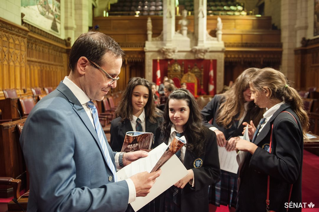 Le sénateur Housakos aide des élèves à compléter les questions d'un tout nouveau cahier d'activités du Sénat.