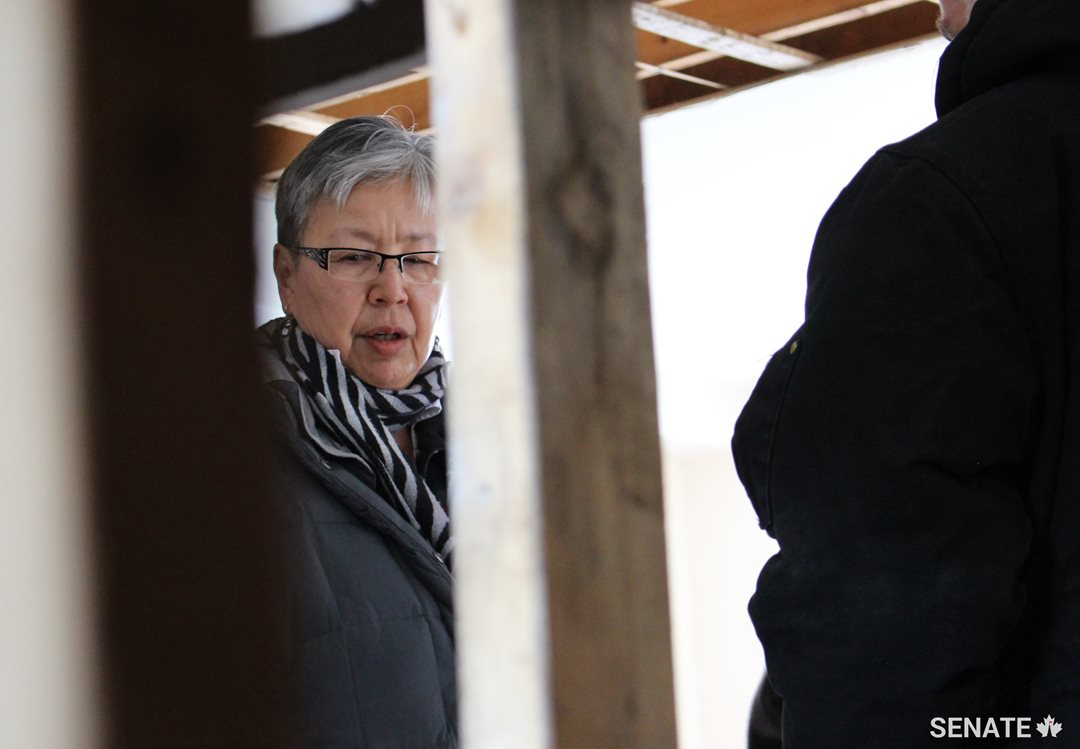 During the committee's fact-finding mission to Inuit Nunangat, Senator Lillian Eva Dyck, chair of the Senate Committee on Aboriginal Peoples, surveys a damaged housing unit in Iqaluit, Nunavut.