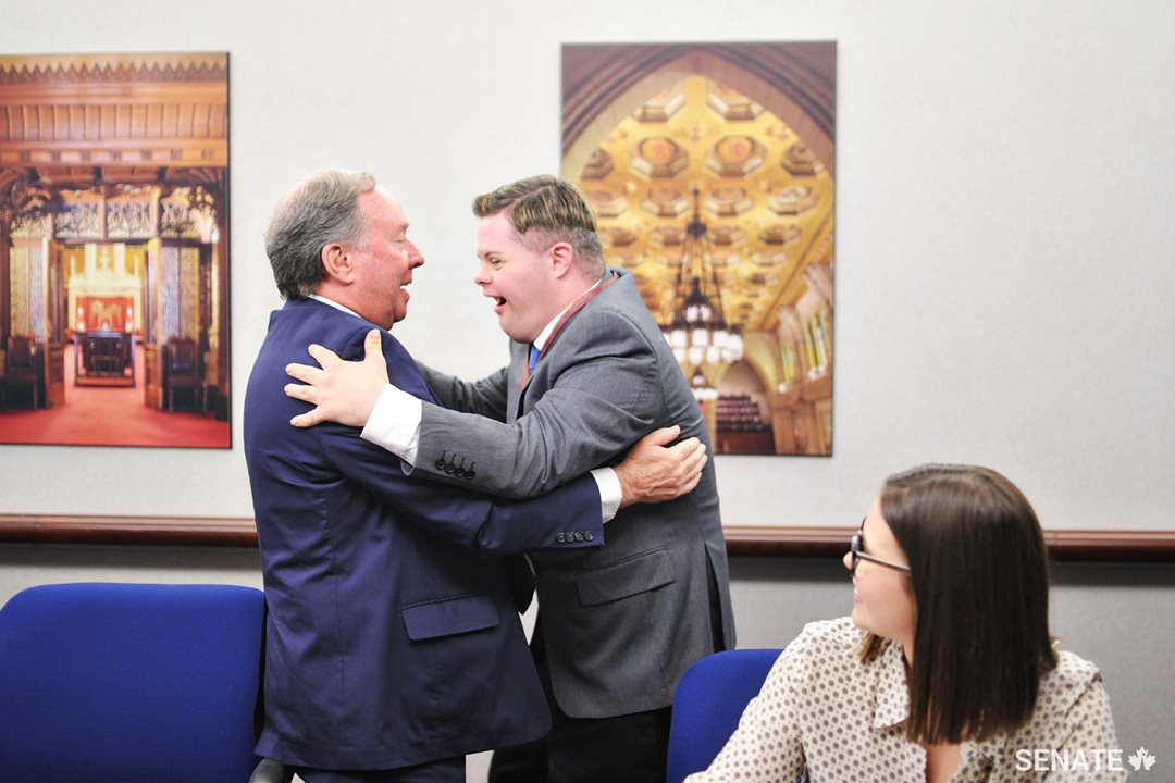 Senator Jim Munson and Michael Hurley-Trinque share a hug at the Friends of the Senate closing ceremony on June 20, 2017.