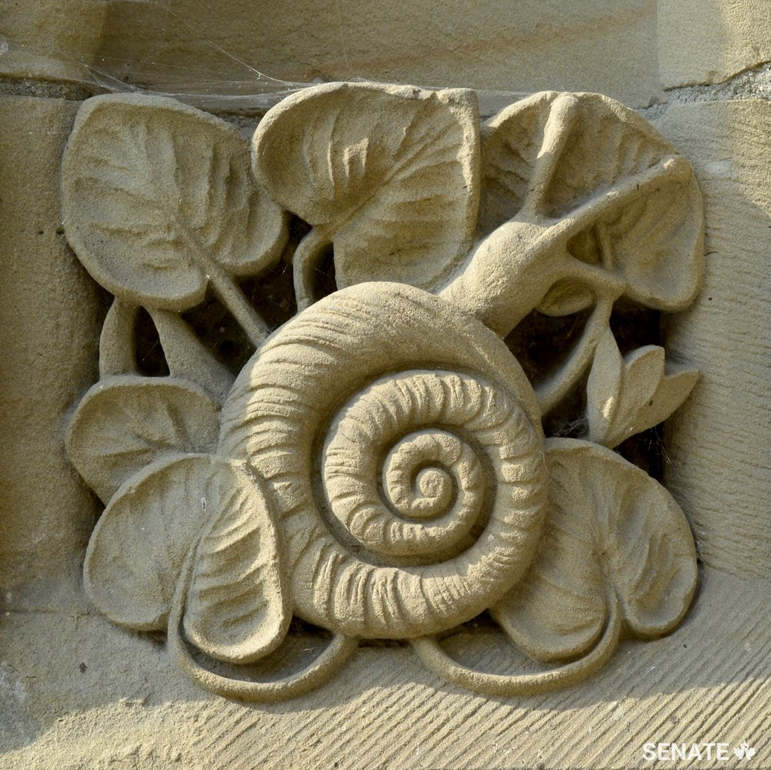 A relief panel depicting a snail adorns the base of the Peace Tower.