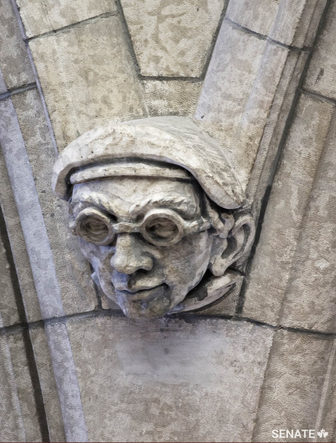 A self-portrait of one of the sculptors who worked on the Senate foyer in the 1950s stares down from high above.
