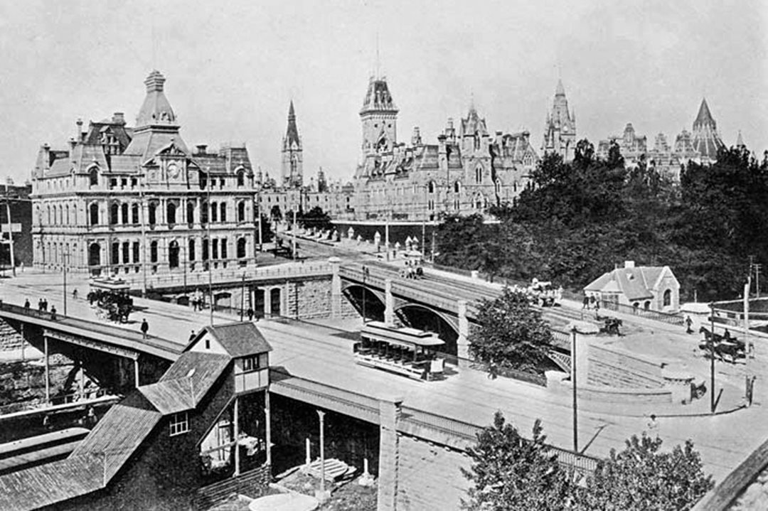 Ottawa's old post office in 1903, with Parliament Hill in the background. In the foreground are Sapper's Bridge, built in 1827 and, behind it, Dufferin Bridge, built in the 1870s. Both were torn down and replaced with a single structure, today's Plaza Bridge, during construction of Union Station. (Library and Archives Canada)