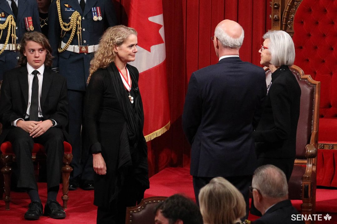 Chief Justice of Canada, Beverley McLachlin (centre) administers the formal oaths of office as Governor General Designate Julie Payette's son, Laurier Payette Flynn, sits close by.