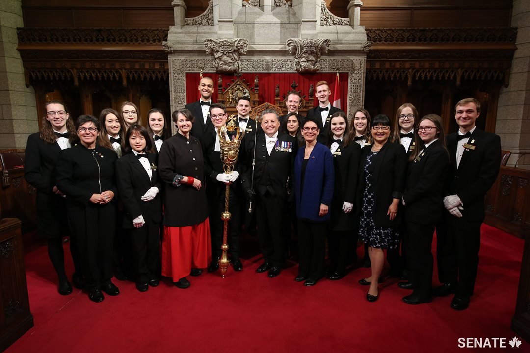 The Senate pages are joined in front of the throne by Senator Kim Pate, Senator Marilou McPhedran, Usher of the Black Rod J. Greg Peters, Senator Raymonde Gagné and Senator Yonah Martin.