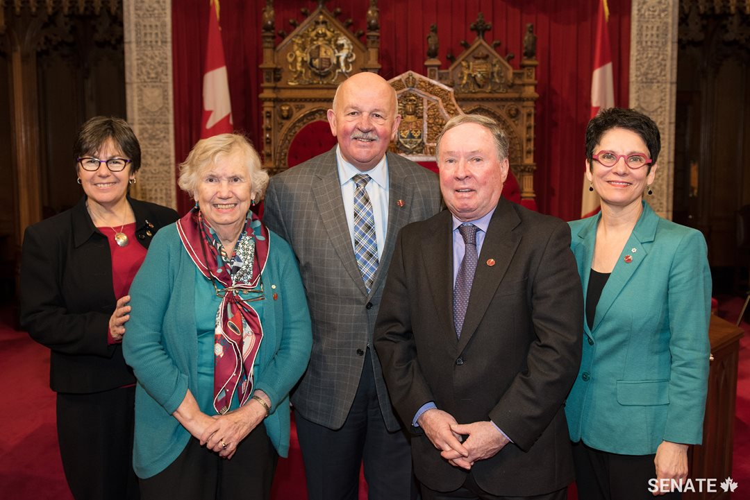 From left, Senator Kim Pate, former senator Landon Pearson and senators Terry Mercer, Jim Munson and Raymonde Gagné celebrate National Child Day in the Red Chamber.