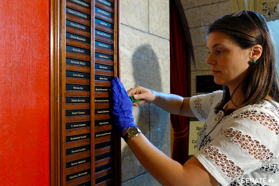 Senate Heritage and Curatorial Services Project Co-ordinator Tamara Dolan unscrews the wooden side rail of the Senate Seniority Board to insert a new nameplate.