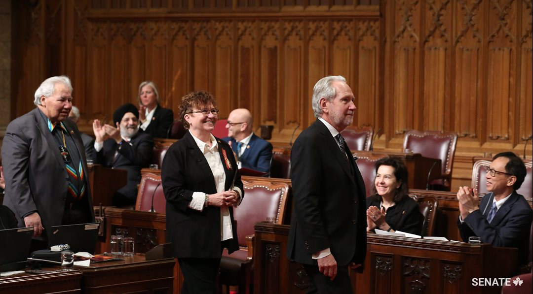 Senator Yvonne Boyer (centre), joined by Senator Peter Harder (right) and Senator Murray Sinclair (left), is welcomed into the Senate Chamber.