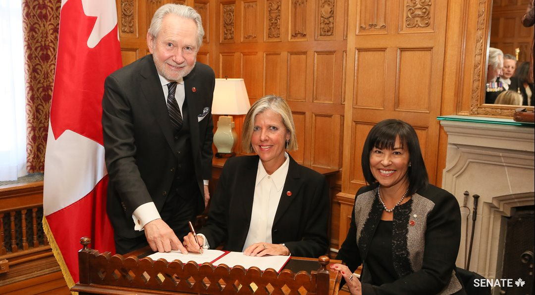 Senator Marty Deacon (centre) joins the Senate, flanked by Senator Peter Harder (left) and Senator Chantal Petitclerc (right).