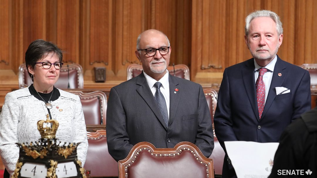 Senator Mohamed-Iqbal Ravalia, centre, is sworn in as senators Kim Pate and Peter Harder look on.