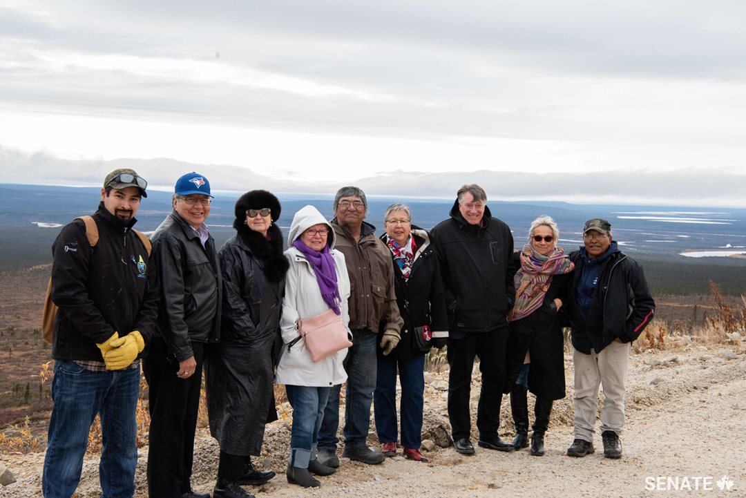 Senators join Old Crow community leaders on a tour to the top of a mountain. During the tour of the community, committee members saw impressive infrastructure including a large solar power project and a centre where researchers are studying permafrost.