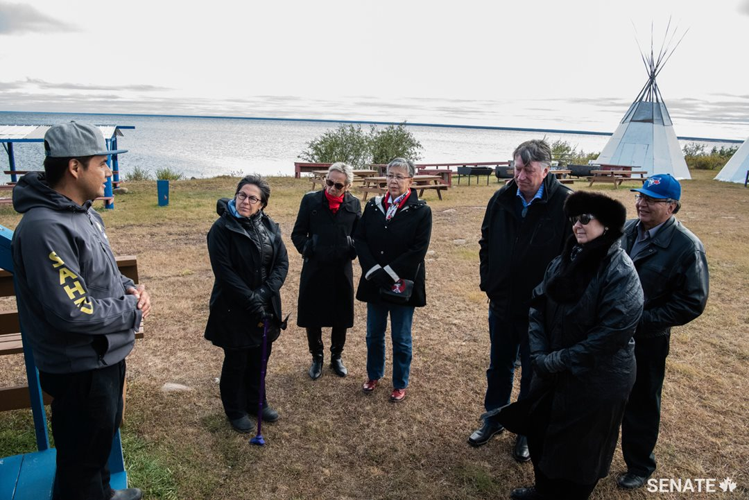 Senators Kim Pate, Mary Jane McCallum, Lillian Eva Dyck, Scott Tannas, Marilou McPhedran and Dan Christmas take a tour of Délįne to learn about the community's rich history. Délįne's people are guided by four prophets—most notably the Prophet Ayah, a Dene spiritual leader from the community who lived there until the mid-1900s.