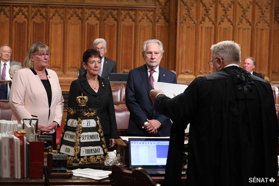 La sénatrice Bev Busson, au centre, est accompagnée de la sénatrice Gwen Boniface et du sénateur Peter Harder dans la Chambre du Sénat lors de sa cérémonie d'assermentation qui a eu lieu le 27 septembre 2018.