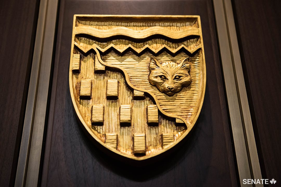 The shield of the Northwest Territories features a wavy diagonal line representing the tree line, a horizontal one representing the Northwest Passage and a white fox and gold bars symbolizing the North's fur and mineral wealth respectively.