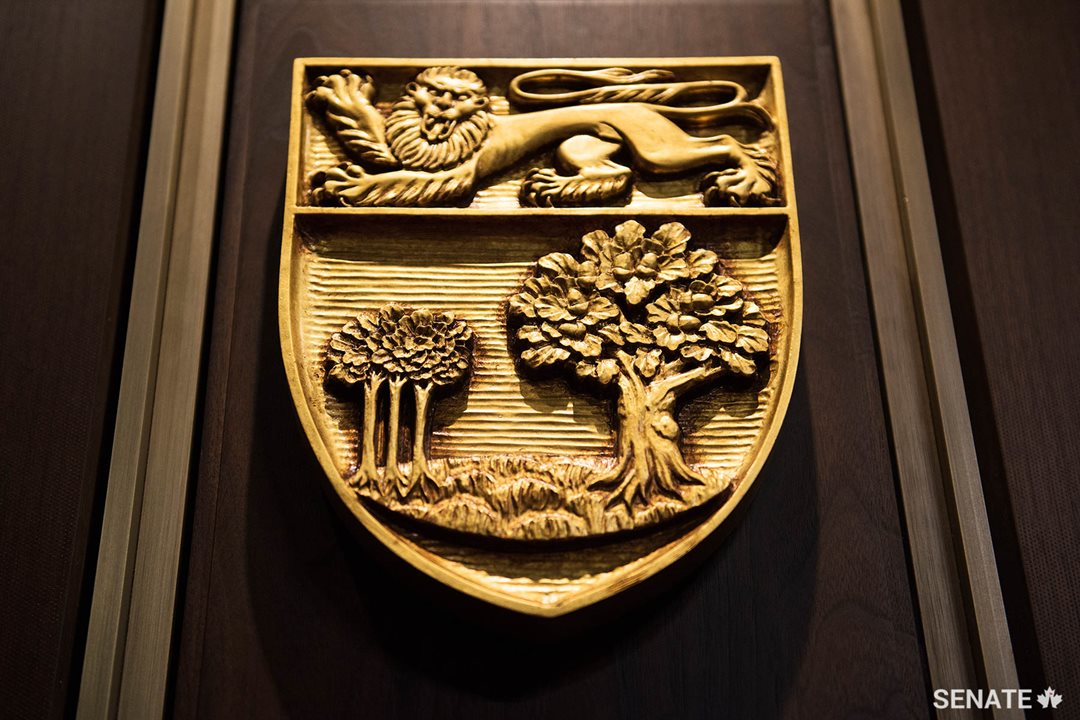 Prince Edward Island's shield features an oak tree and three saplings, representing the province's three counties, below an English lion.