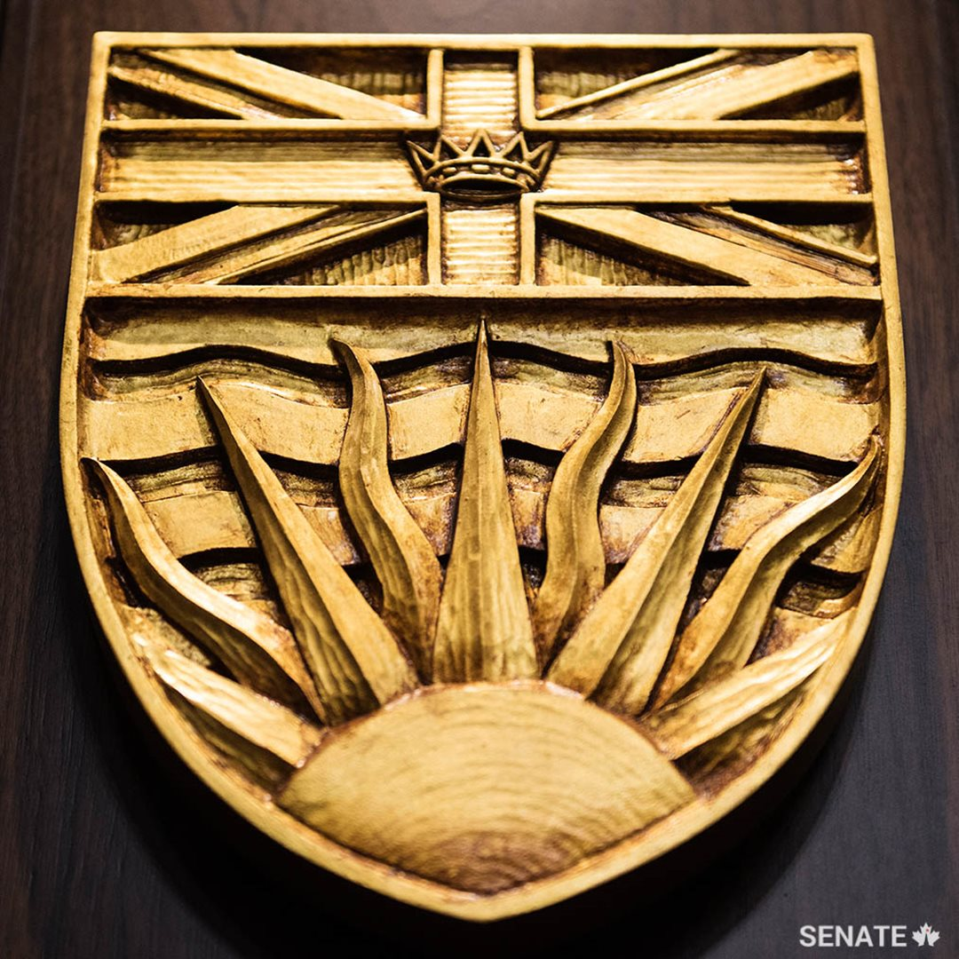 British Columbia's provincial shield features the Union Flag and a crown above a depiction of the sun setting over the Pacific Ocean. It is one of 15 carvings recently installed in the new Senate Chamber.