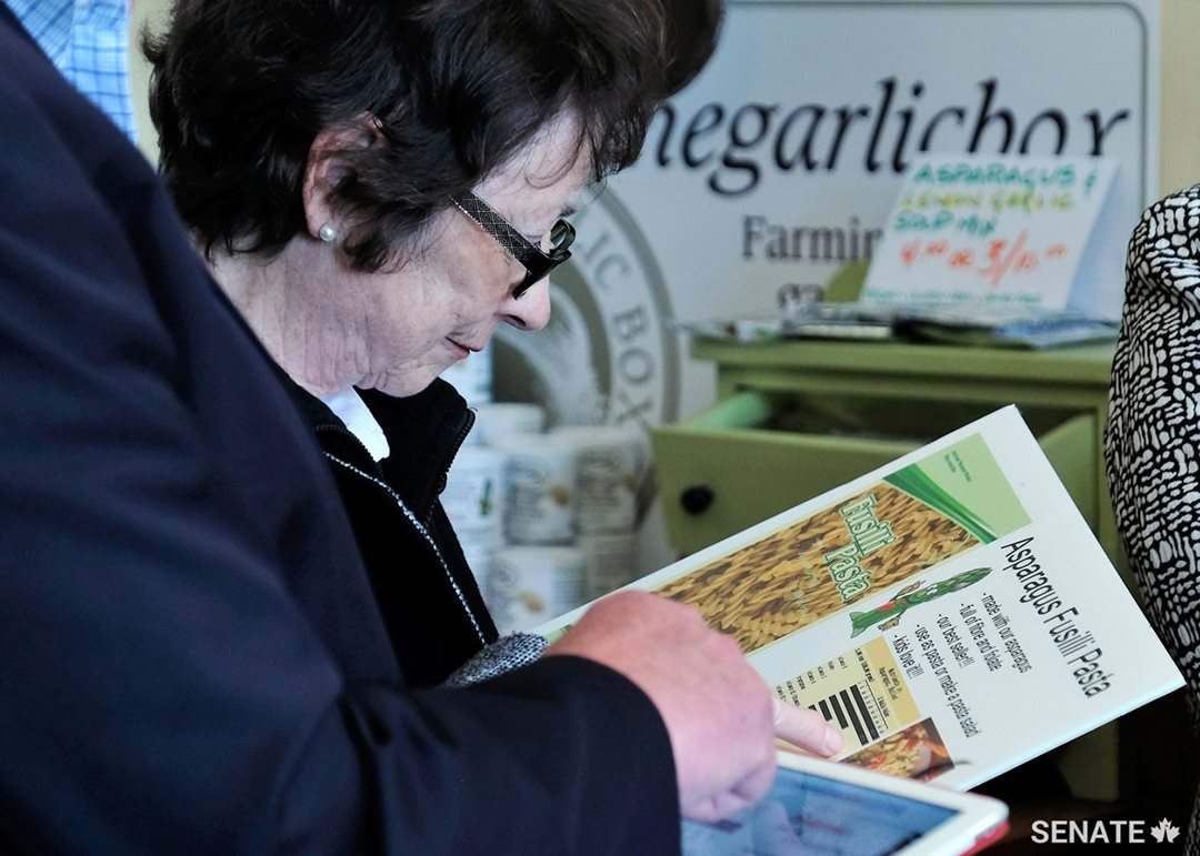 Senator Diane Griffin reads about the health benefits of asparagus pasta, an innovative, value-added food offered by a small family business in Cambridge, Ont.