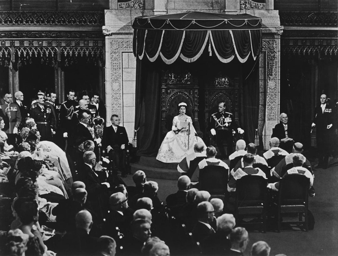 In the Senate Chamber with Prince Philip beside her, Queen Elizabeth II reads the Speech from the Throne to open Canada's 23rd Parliament on October 14, 1957. (Library and Archives Canada)