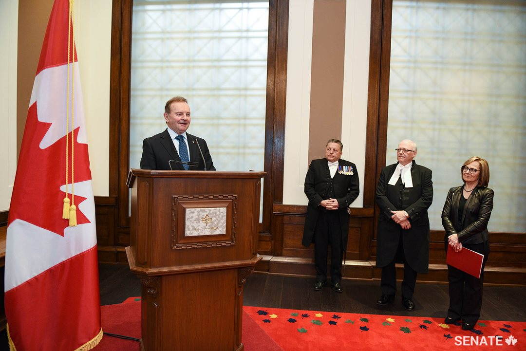 Senator Joyal delivers remarks during an event celebrating the book launch at the Senate of Canada building on May 14, 2019. Listening, from right, are Senator Seidman, Speaker of the Senate George J. Furey and Usher of the Black Rod J. Greg Peters.
