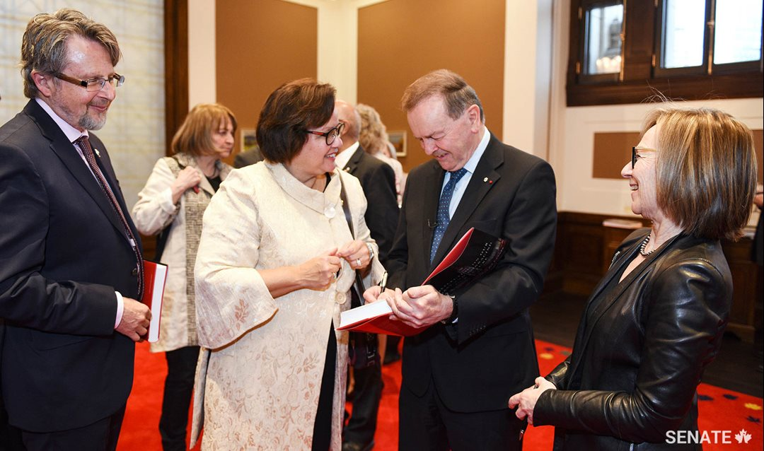 Senators Stan Kutcher and Rosemary Moodie look on as Senator Serge Joyal and Judith G. Seidman co-sign their copies of <em>Reflecting on our Past and Embracing our Future: A Senate Initiative for Canada</em> (Left to right: Senators Kutcher, Moodie, Joyal and Seidman).