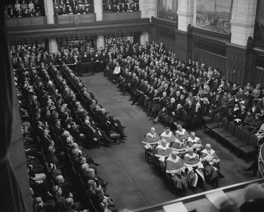 During the opening of the 22nd Parliament in 1953, an expanded roster of nine Supreme Court judges sat on hard-backed chairs. (Library and Archives Canada)