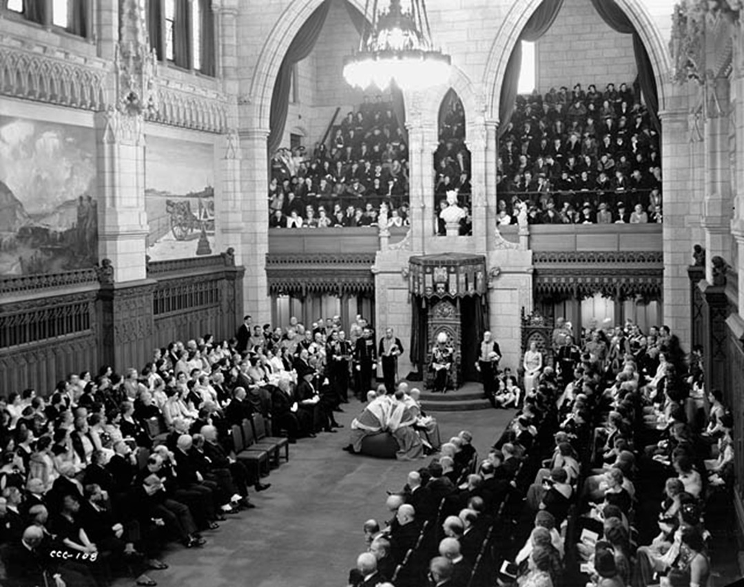 Governor General Lord Tweedsmuir reads the Speech from the Throne during the opening of the third session of Canada's 18th Parliament in 1938. Directly in front of him, Canada's Supreme Court judges sit on the woolsack. (Library and Archives Canada)